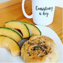 Plate of Five Seed Roll with slices of cantaloupe next to a mug with the words 'Consistency is key' on it